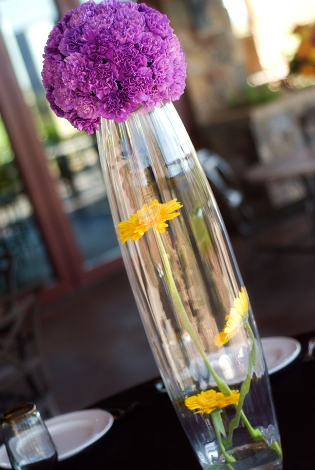 Creative summer wedding centerpiece with purple carnations and yellow gerbera daisy